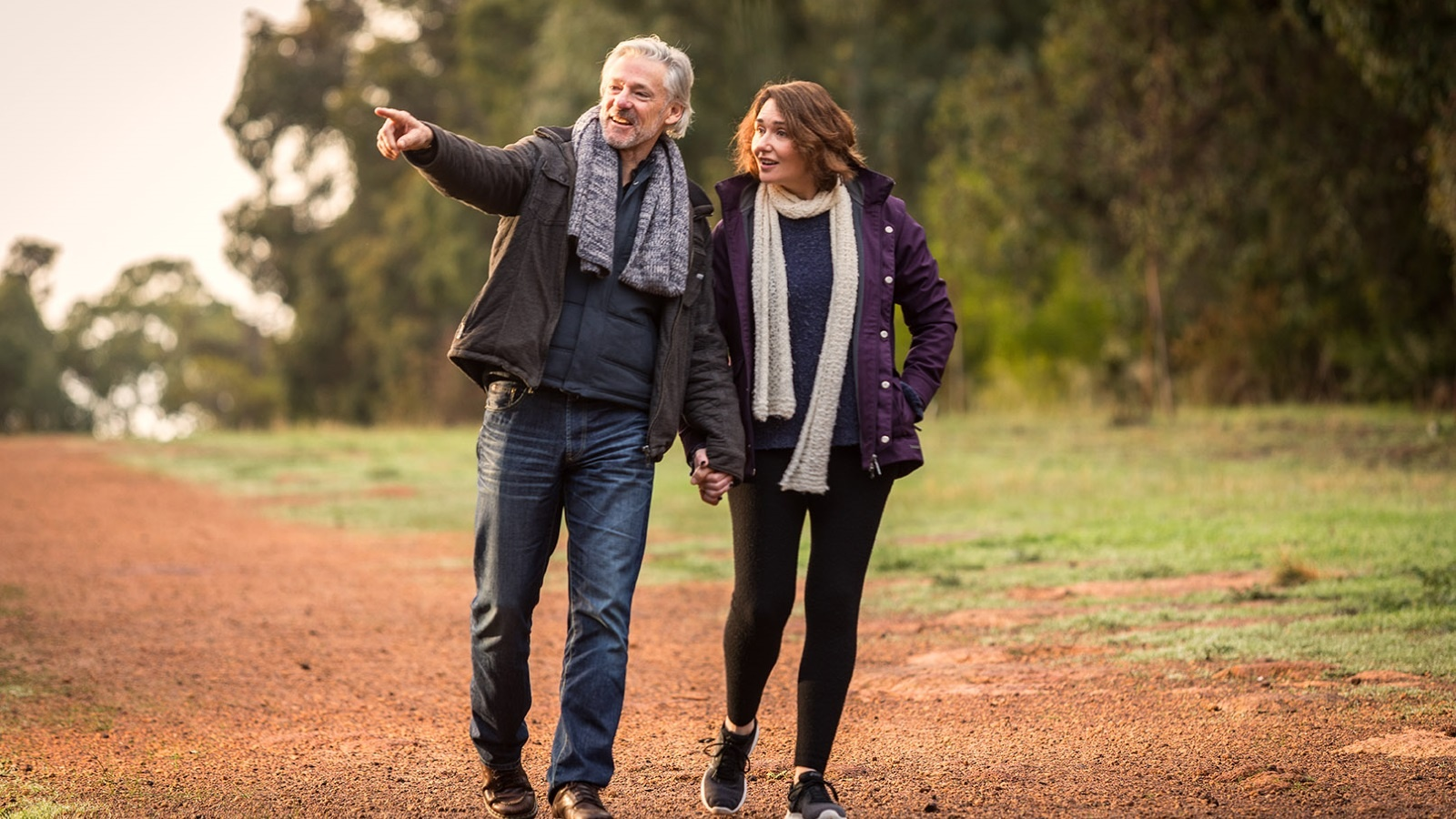 Happy middle aged couple walking outside in the nature holding hands| Rural Home Builders WA