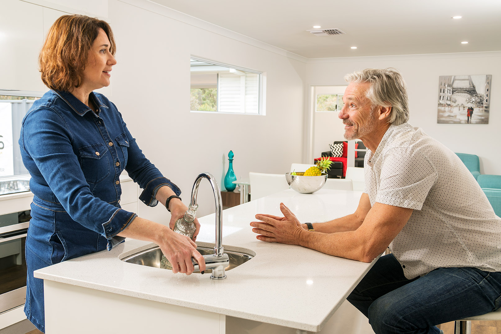 Middle aged couple sitting and standing in the kitchen talking to each other | Modular Homes Perth