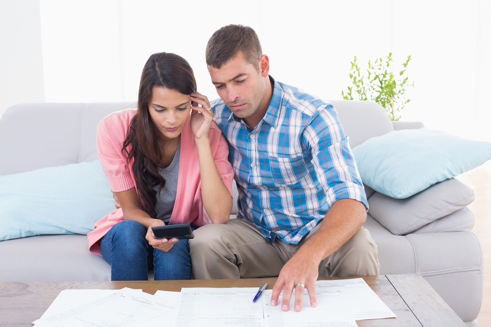 Couple calculating home finances together at table in house