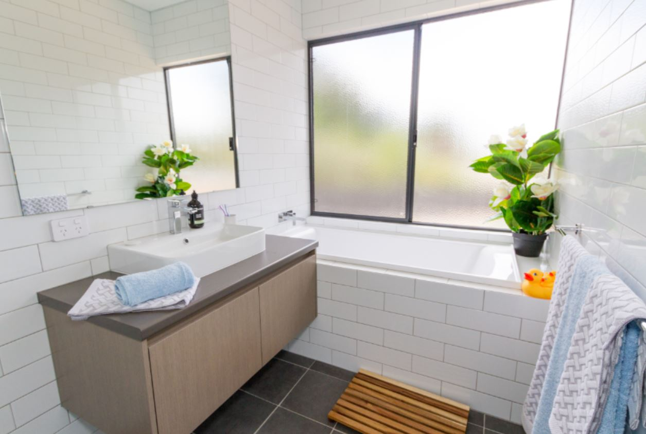 Bathroom with white sink and big window surrounded by white and grey tiles | Evoke Living Homes