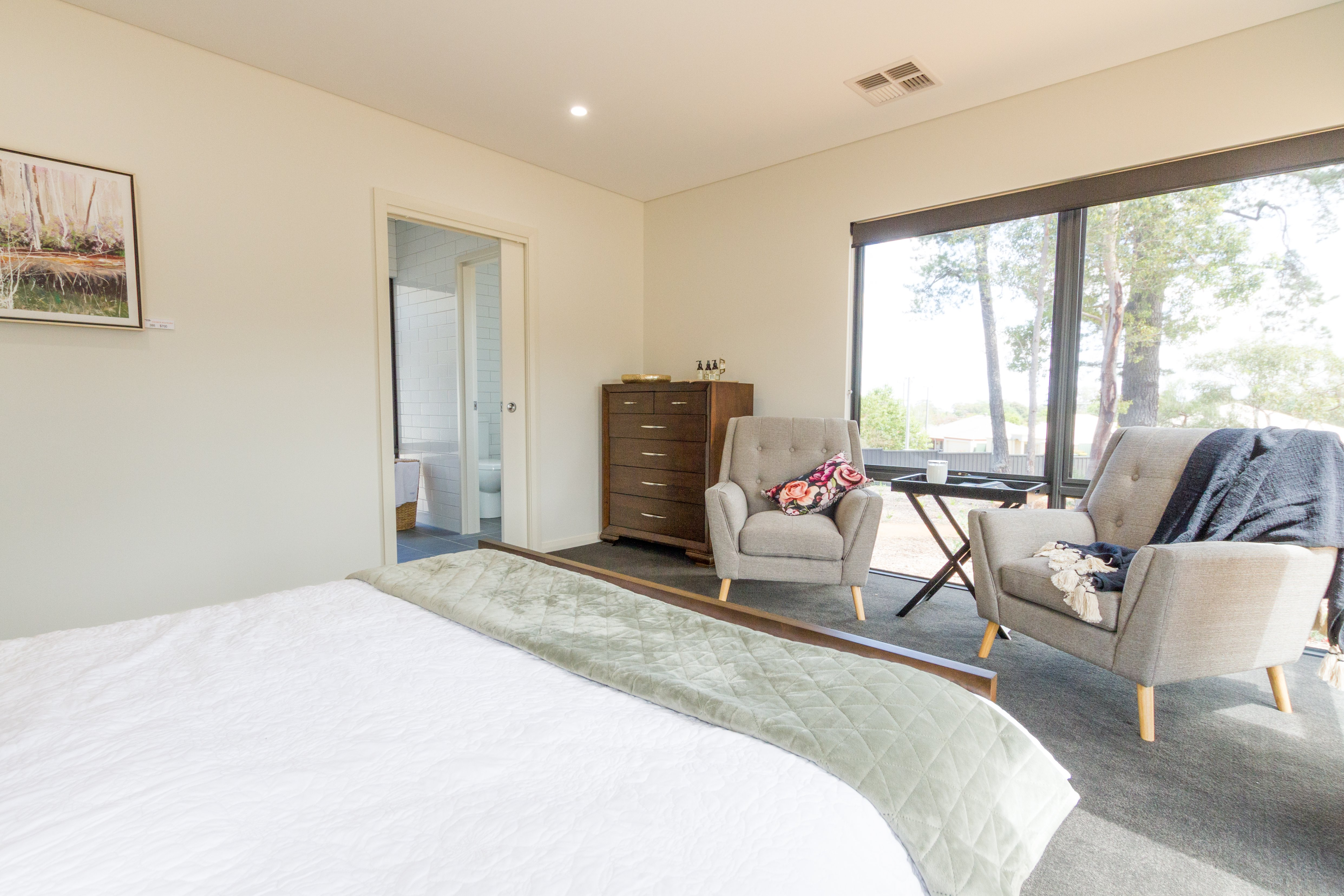 Bedroom with queen sized bed and two seats overlooking a big window | Transportable Homes Perth