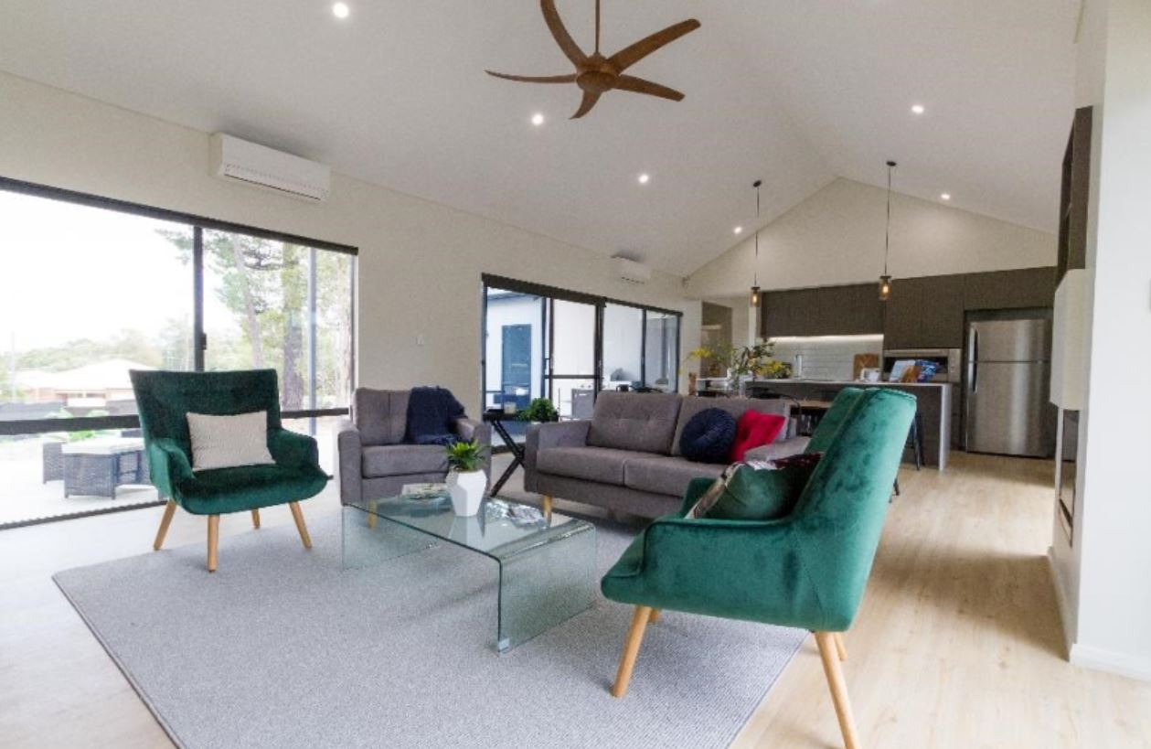 Living Room with Double Seater Grey Couch and Two Green Couches and a Glass Coffee Table | Modular Homes WA