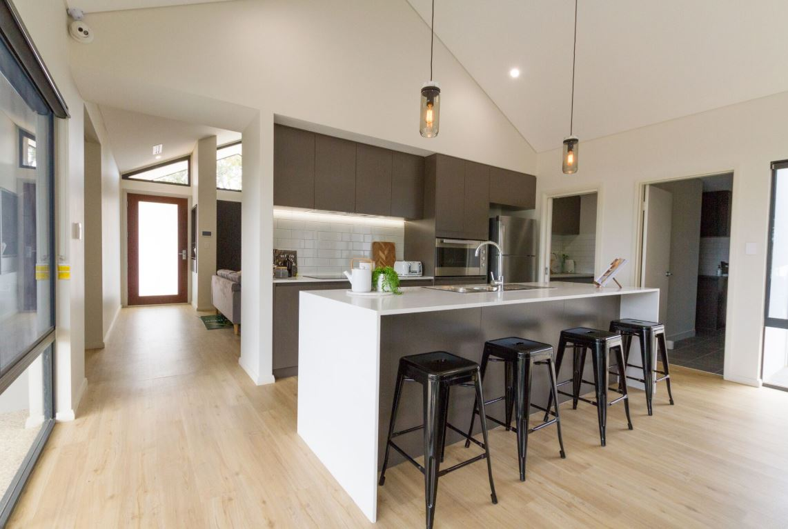 Kitchen with benchtop and a dining table and fan hanging from the roof | Home Builders WA