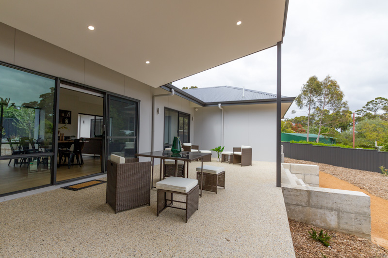 Outdoor living area with a porch undercover and seats with a table and large door | Modular Homes WA