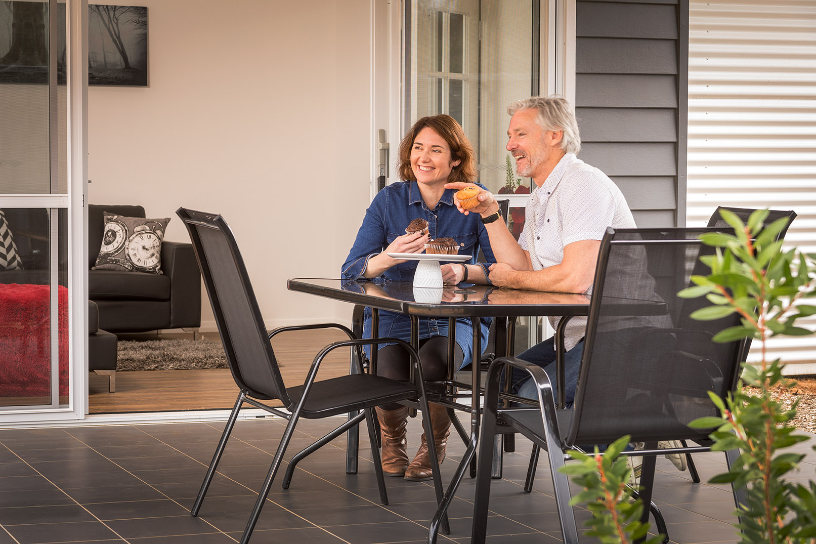 Middle aged couple smiling happily while sitting down in the backyard on their verandah | Modular Homes WA