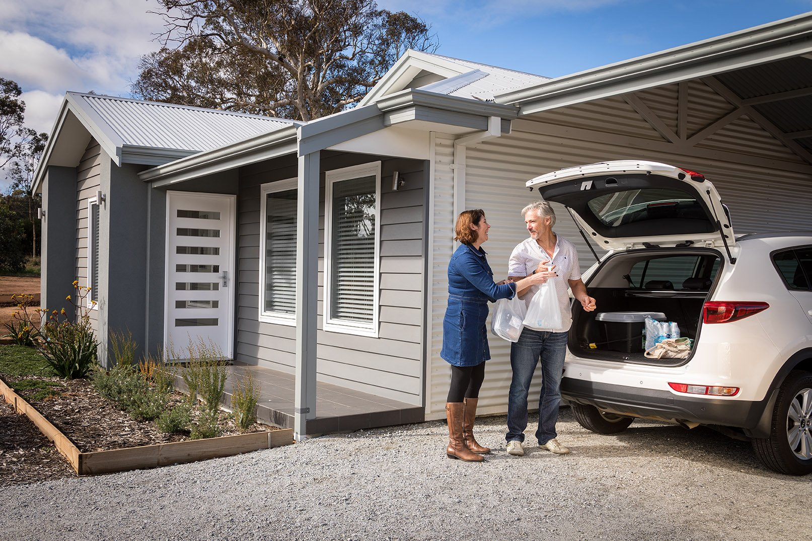 Middle aged couple talking and standing in front of home with car parked under the carport and boot opened | Transportable Homes WA